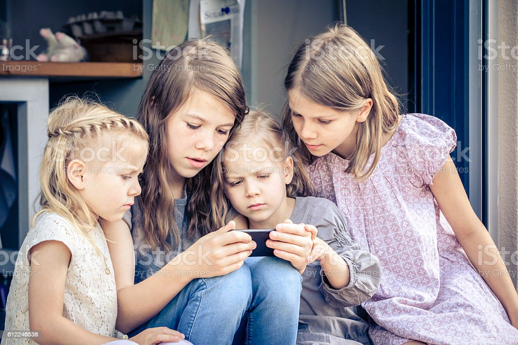 little kids watching cartoons on the mobile phone. stock photo