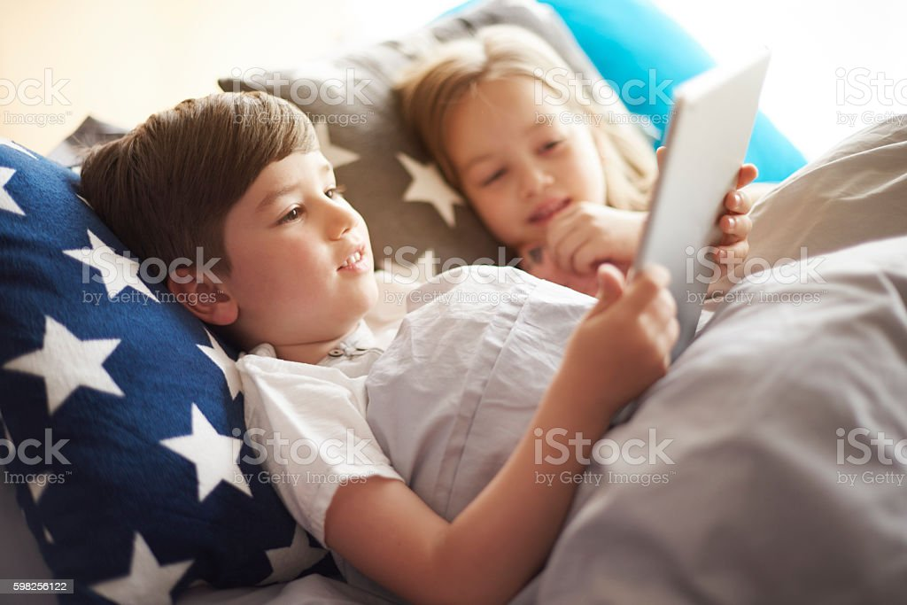 Little kids with digital tablet in bed stock photo