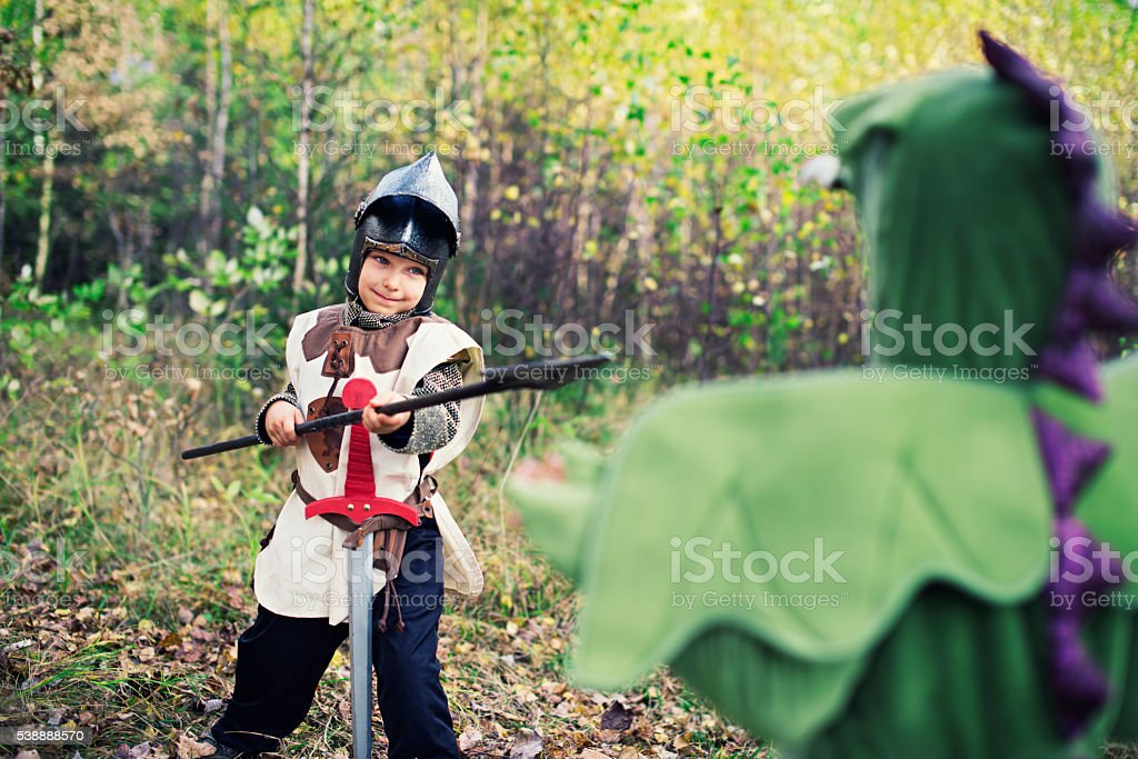 Little knight fighting with green dragon. stock photo