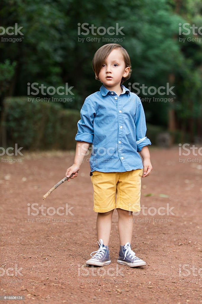 Little latin boy with a stick looking at camera stock photo