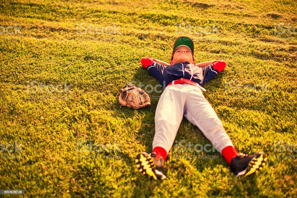 Little League Baseball Boy Relaxes on Field stock photo