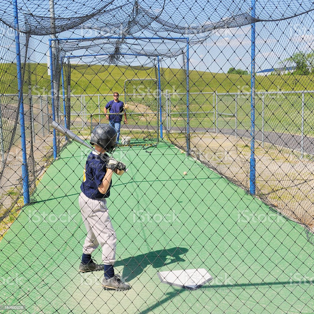 Little League baseball player in batting cage with coach stock photo