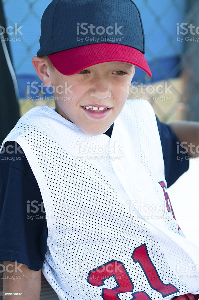 LIttle league baseball player in dugout royalty-free stock photo