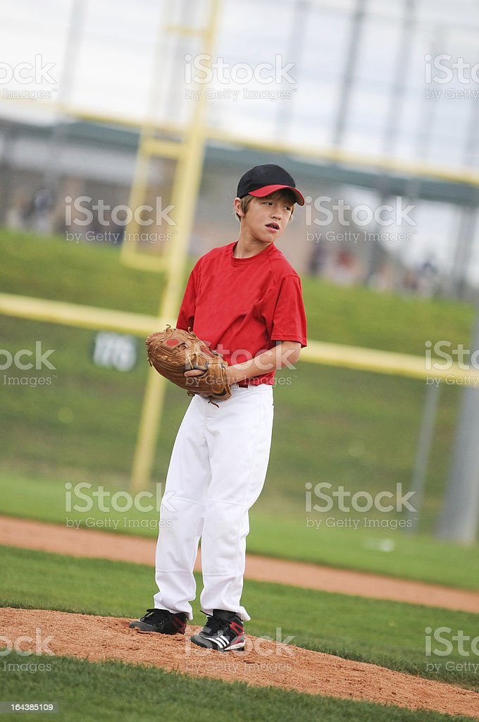Little league pitcher in red looking. stock photo