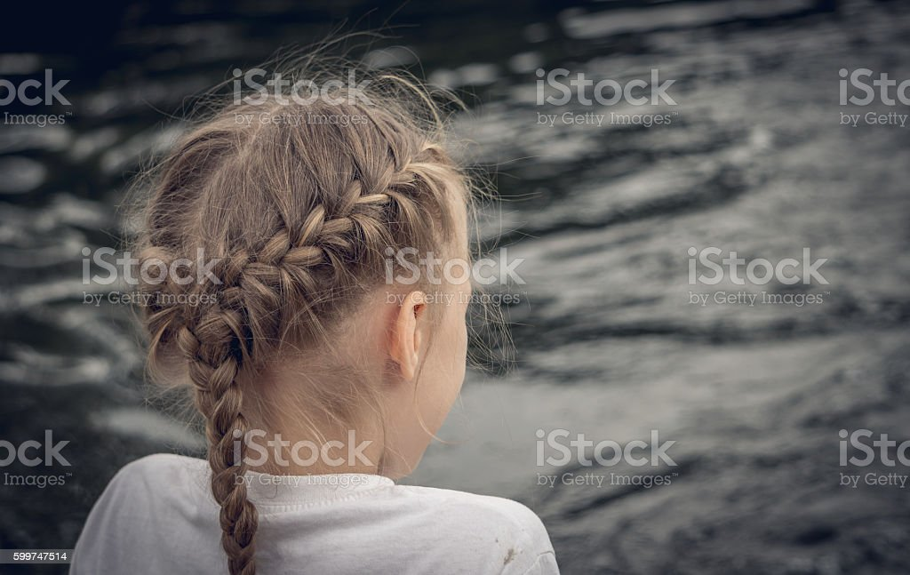 Little lonely girl at the river stock photo