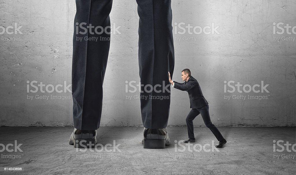 Little man pushes big feet. stock photo