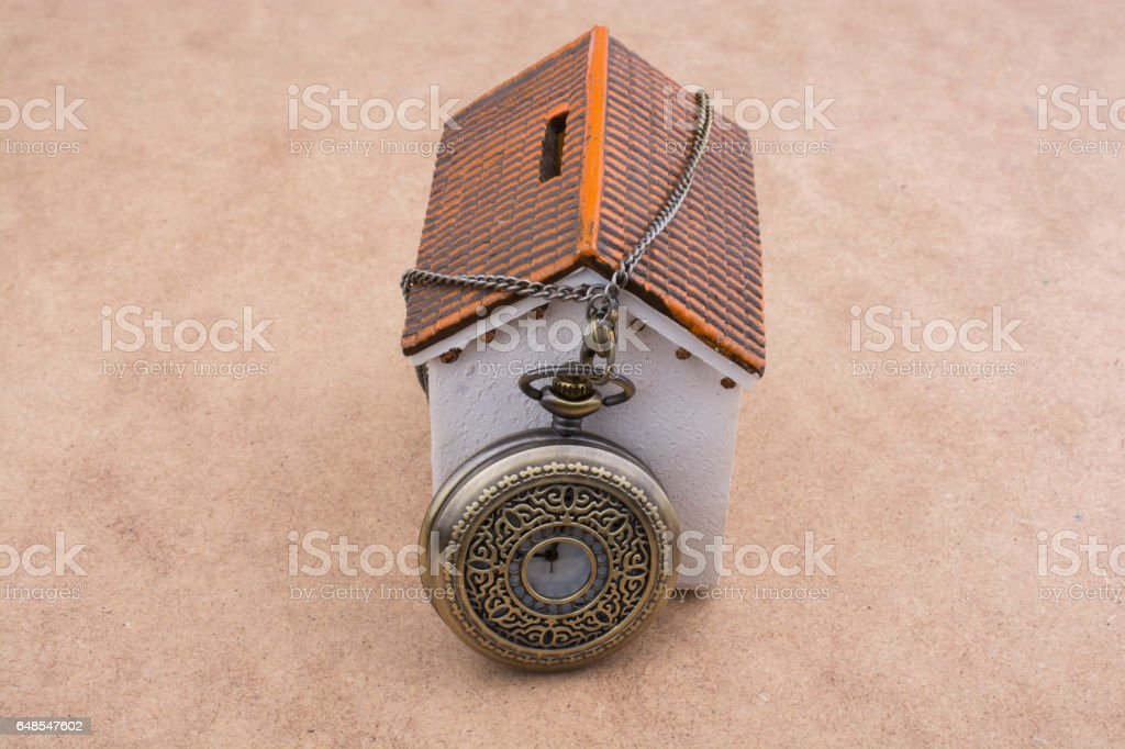 Little model house and a pocket watch stock photo