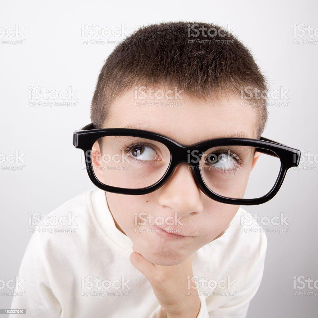 Little Nerd Boy Wearing Large Black Glasses And Thinking stock photo