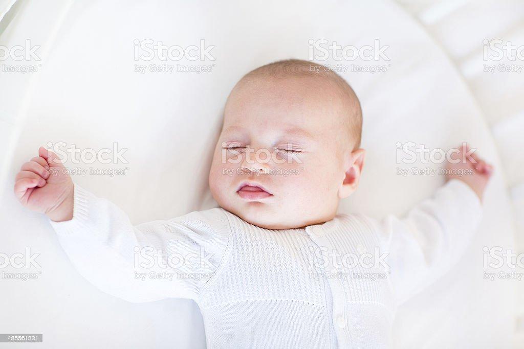 Little newborn baby boy sleeping in round crib with canopy stock photo