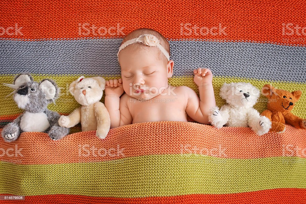 Little newborn girl 11 days, sleeps. Beautiful newborn wiеh teddybear stock photo