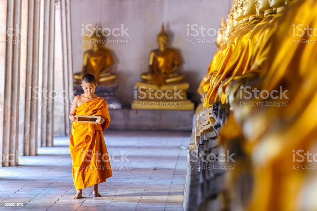 Little novice reading and studying blackboard with funny in old temple, Ayutthaya Province, Thailand stock photo
