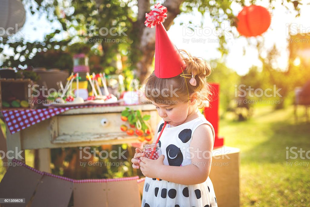 Little party girl drinking juice stock photo