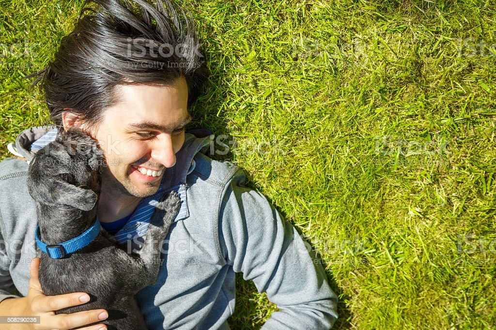 Little Pet Dog and His Owner Having Fun Outdoors stock photo