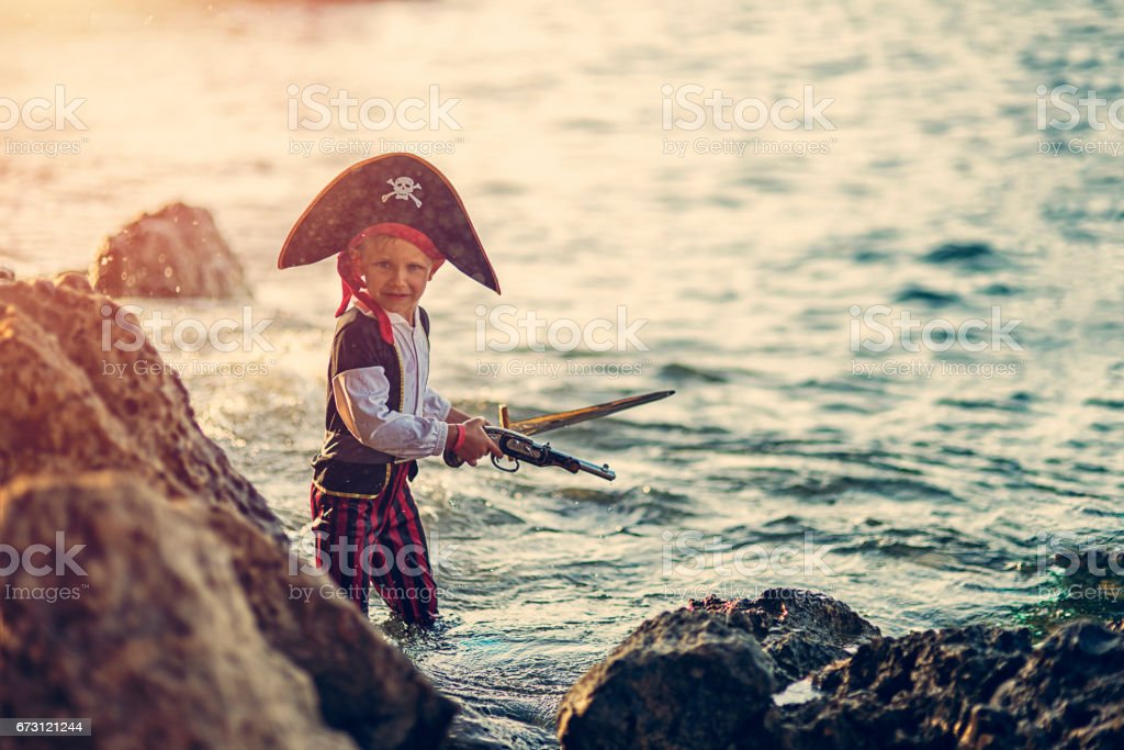 Little pirate looking for a cave to hide his treasure stock photo