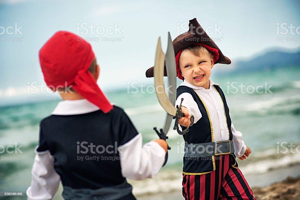 Little pirates fighting on a beach stock photo