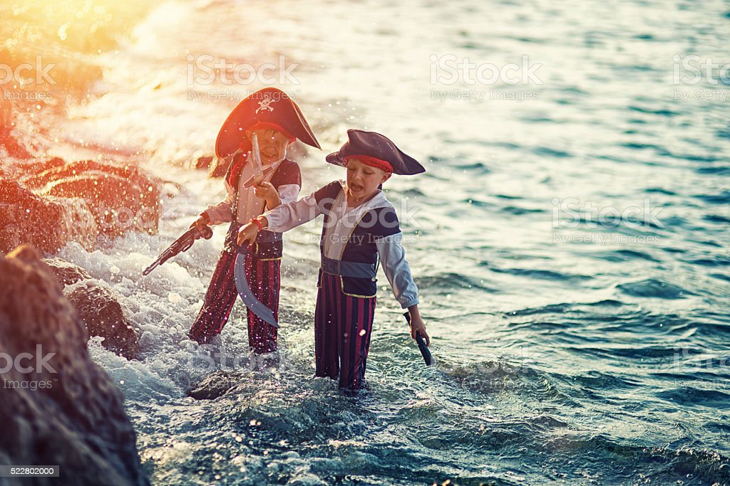 Little pirates playing in sea stock photo