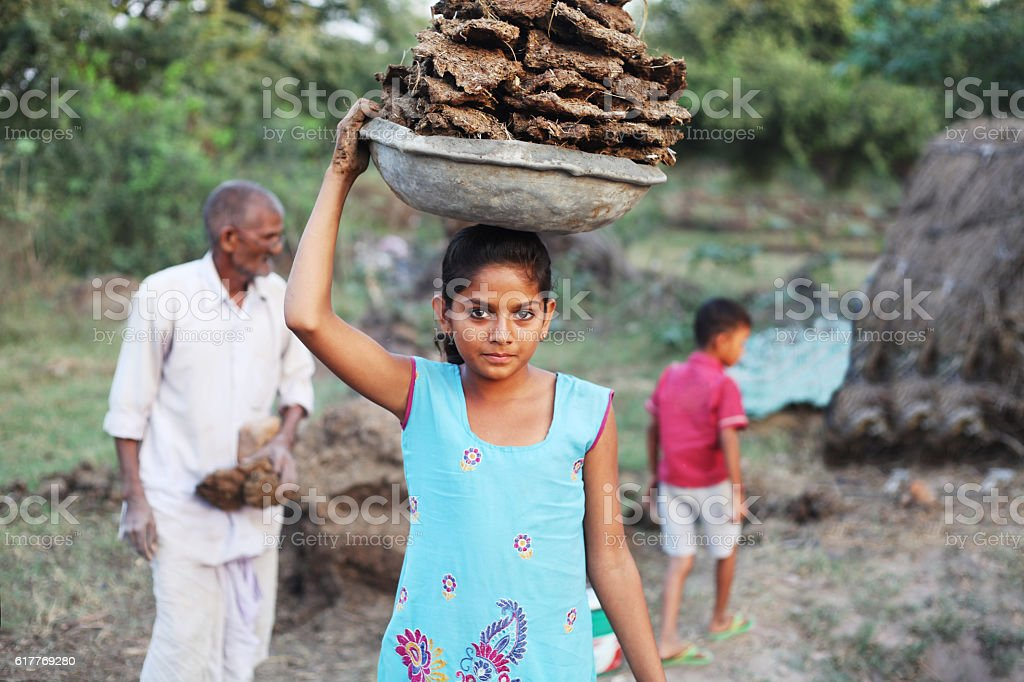 Little poor girl carrying dung cakes stock photo