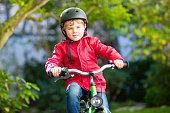 Little preschool kid boy biking on bicycle on autumn