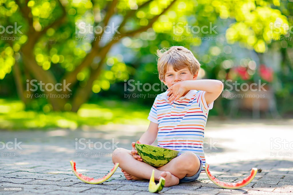 little preschool kid boy eating watermelon in summer stock photo
