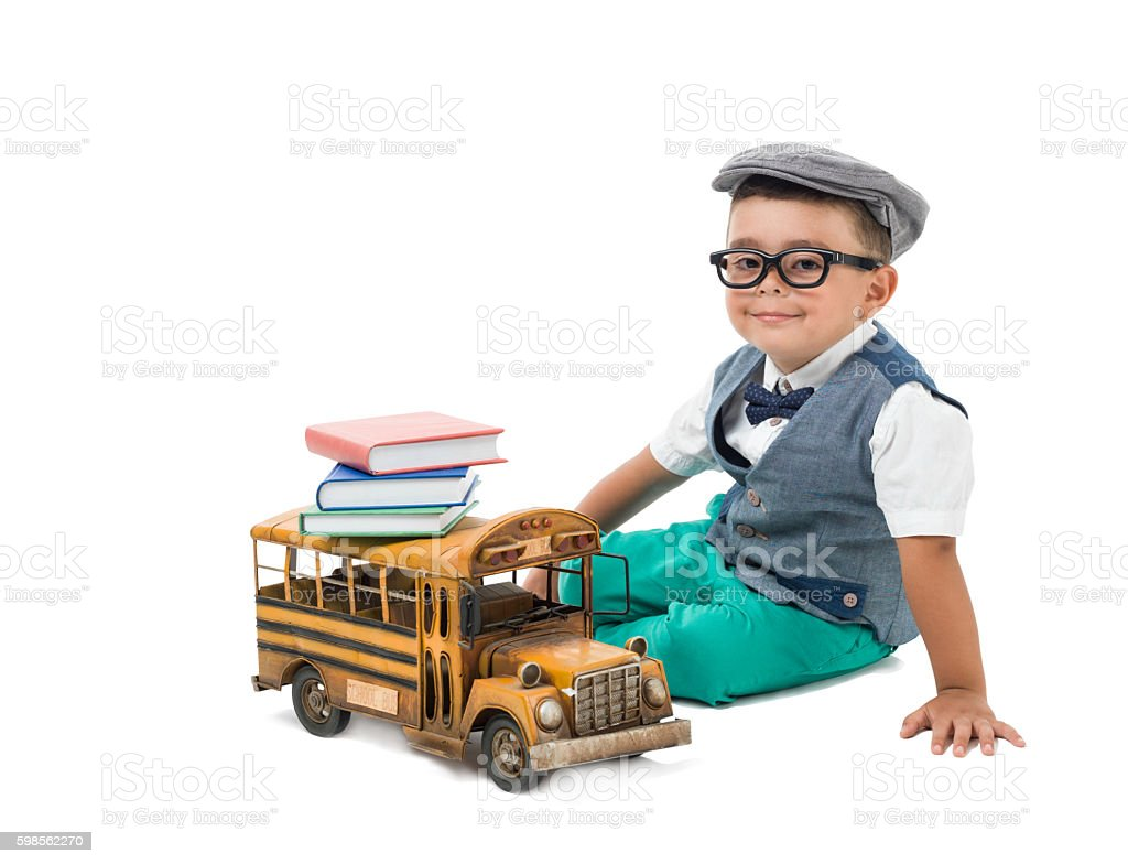 Little preschooler boy playing with schoolbus stock photo
