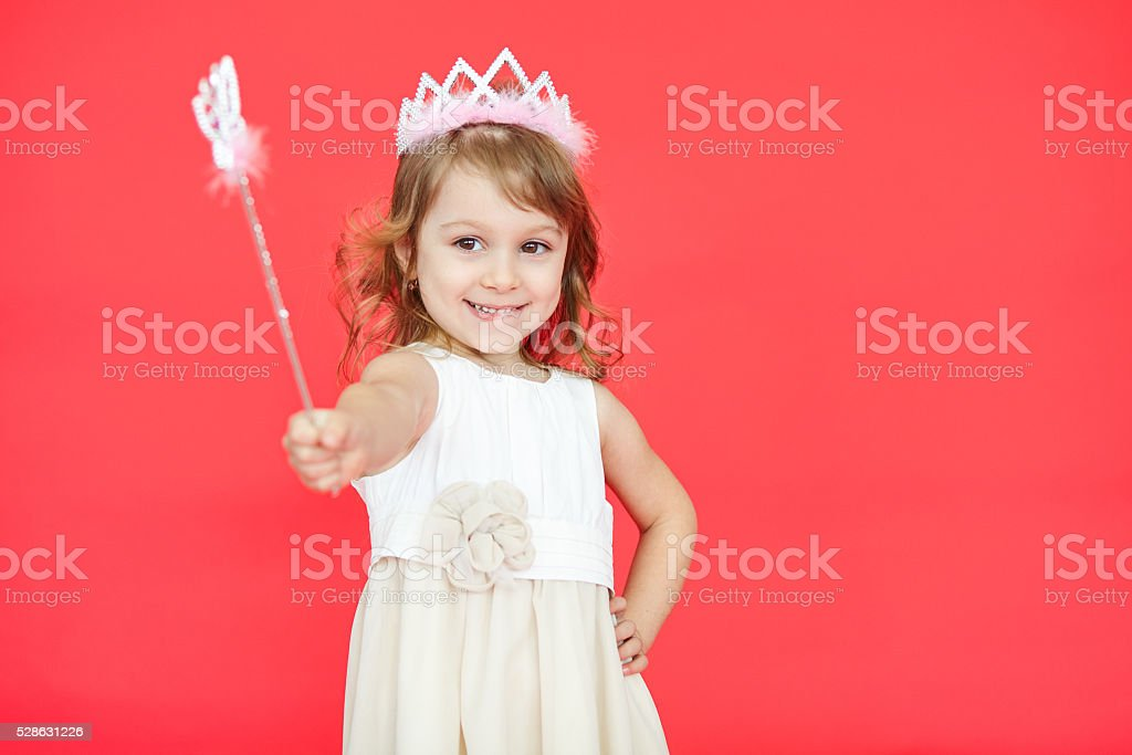 Little princess girl pointing her magic wand towards camera stock photo