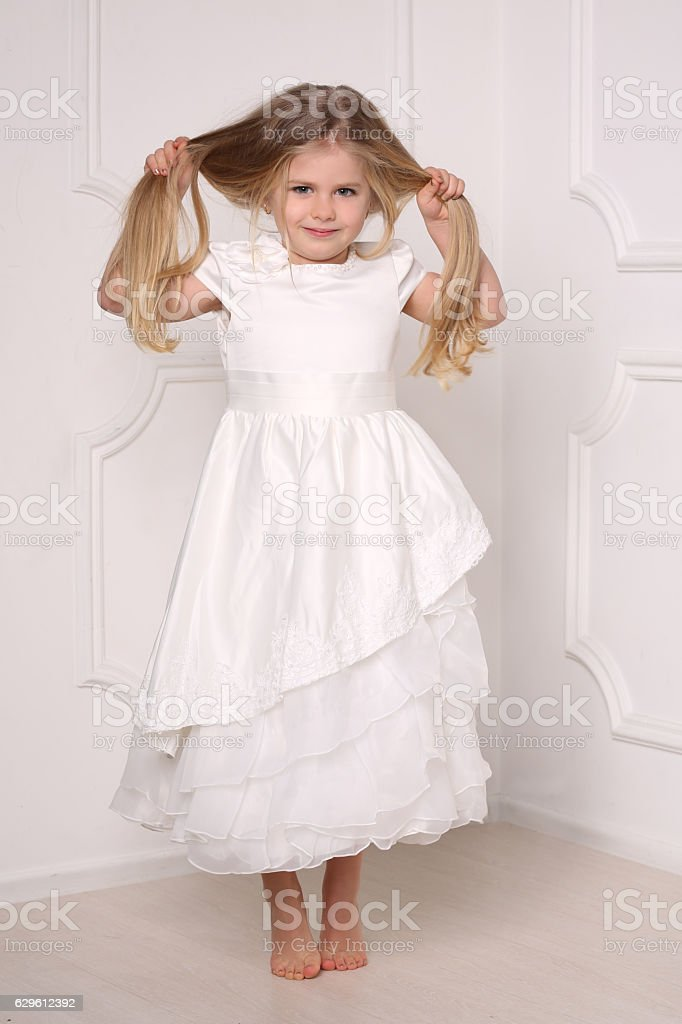 Little princess in dress holding her hairs. White background stock photo