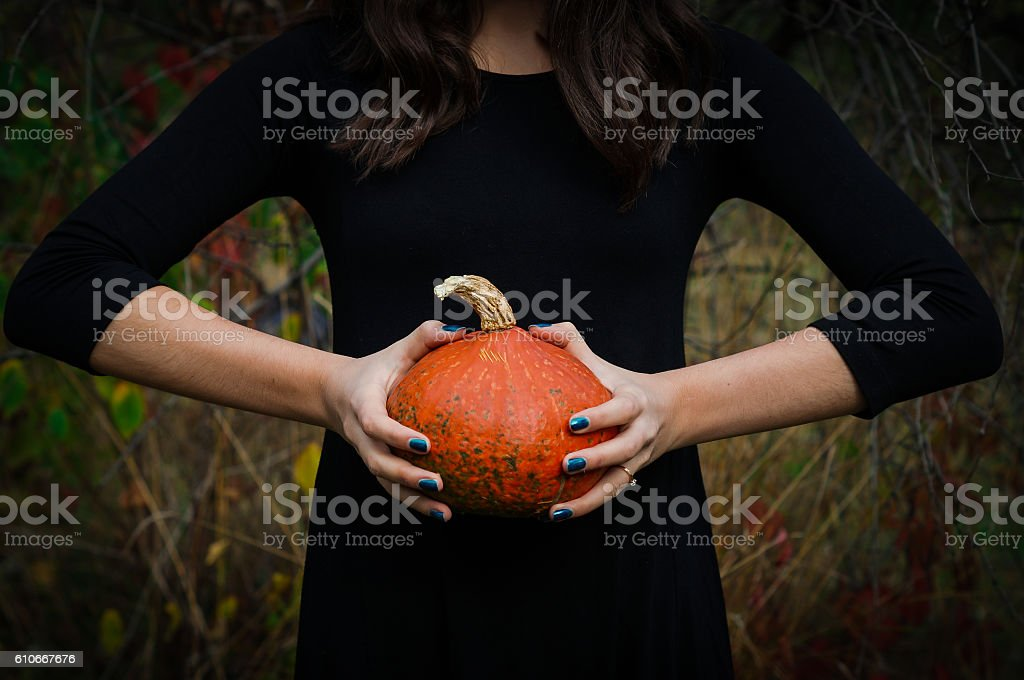 Little pumpkin and girl in the black dress stock photo