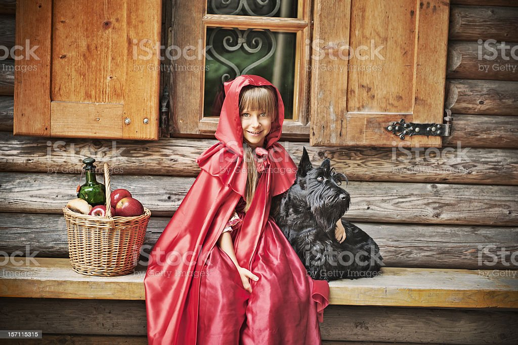 Little Red Riding Hood in front of a cottage stock photo