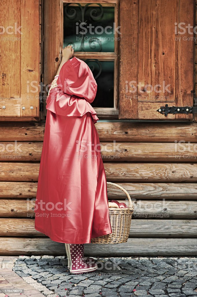 Little Red Riding Hood knocking on window stock photo