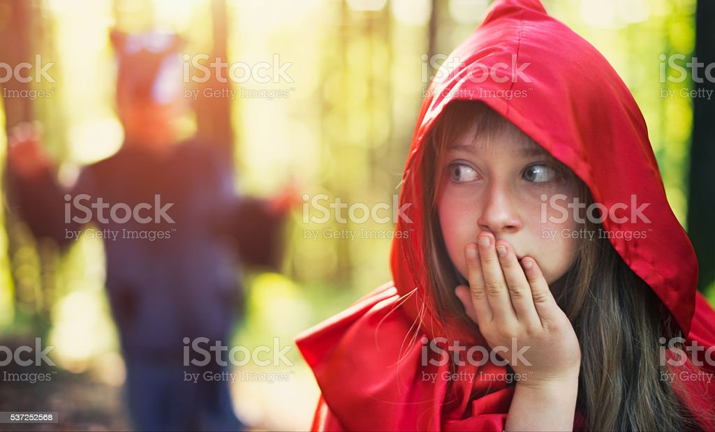 Little Red Riding Hood noticing the wolf stock photo