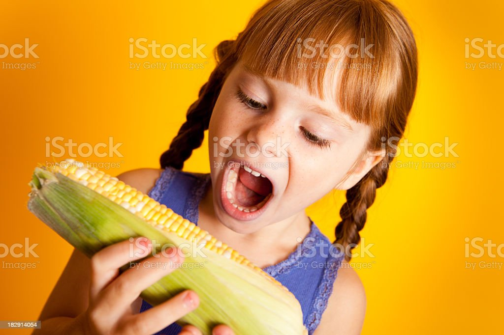 Little Red-Haired Girl Eating Corn on the Cob stock photo