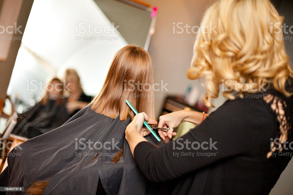 Little Red-Haired Girl Getting Haircut in Salon royalty-free stock photo