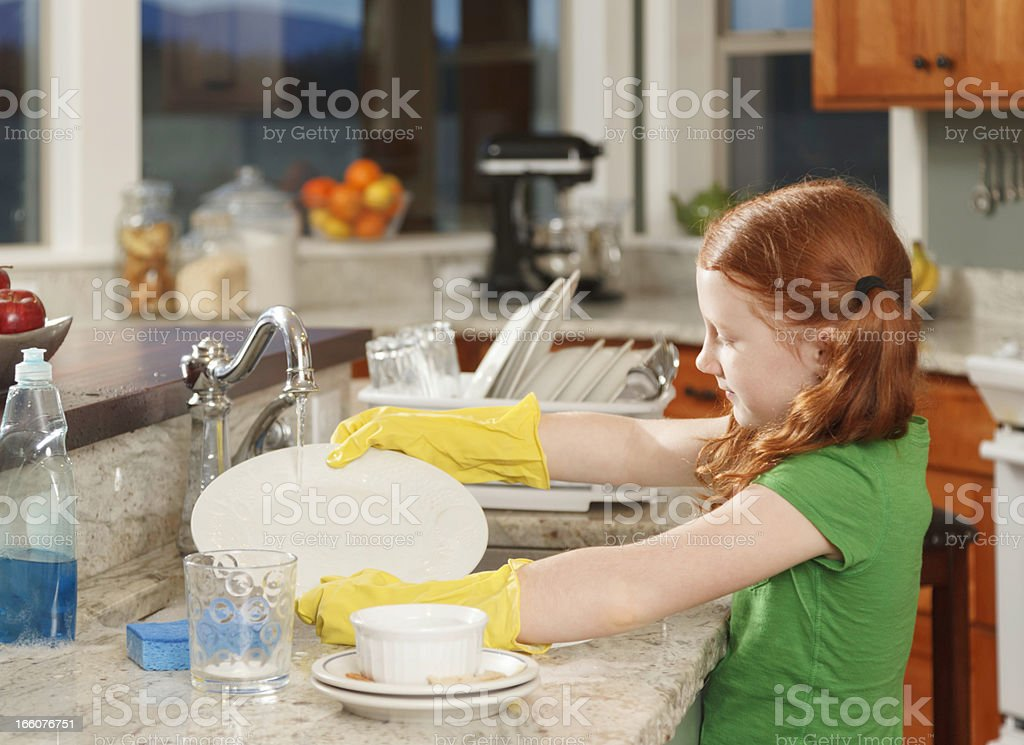 little red-haired girl washing dishes in kitchen sink at home stock photo