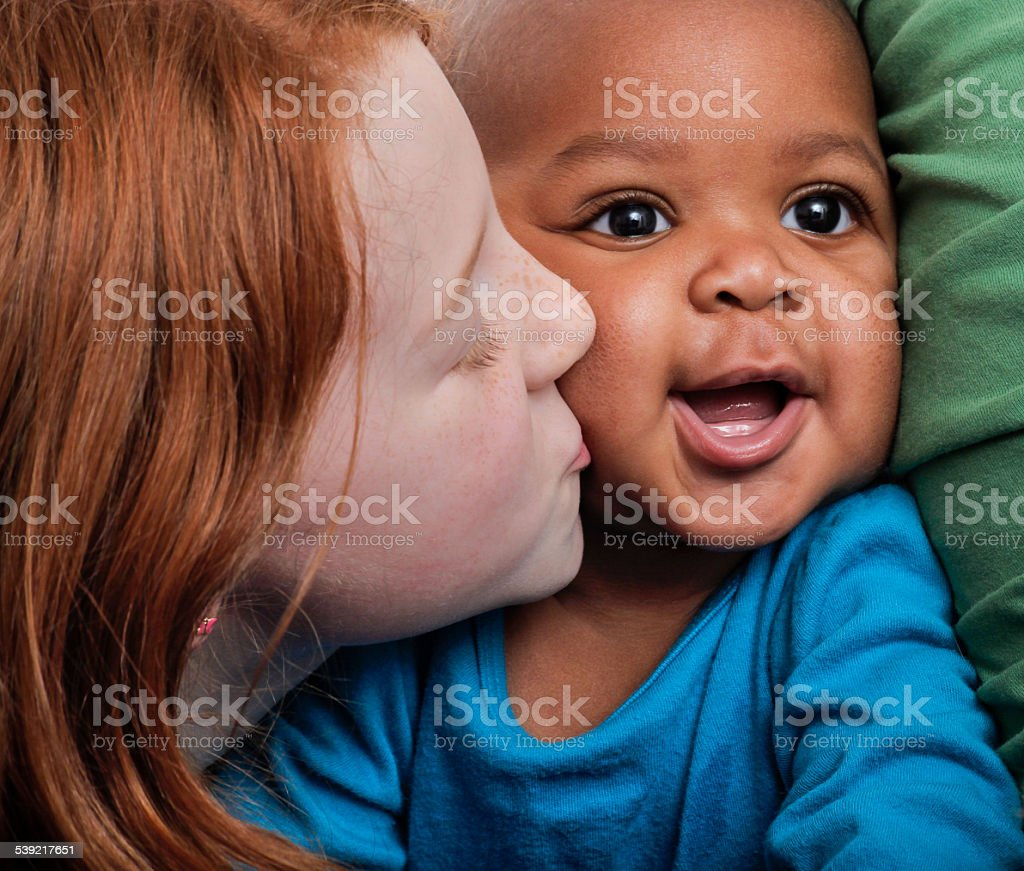 little redhead girl kissing smiling adopted african ethicity baby sister stock photo
