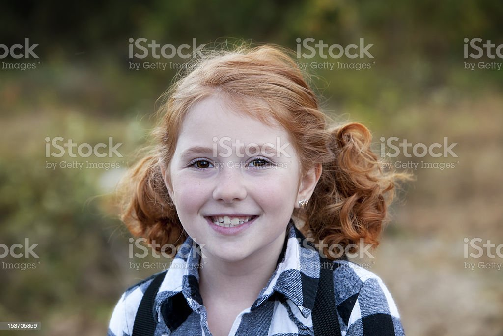 Little redhead girl with pigtails outdoors royalty-free stock photo