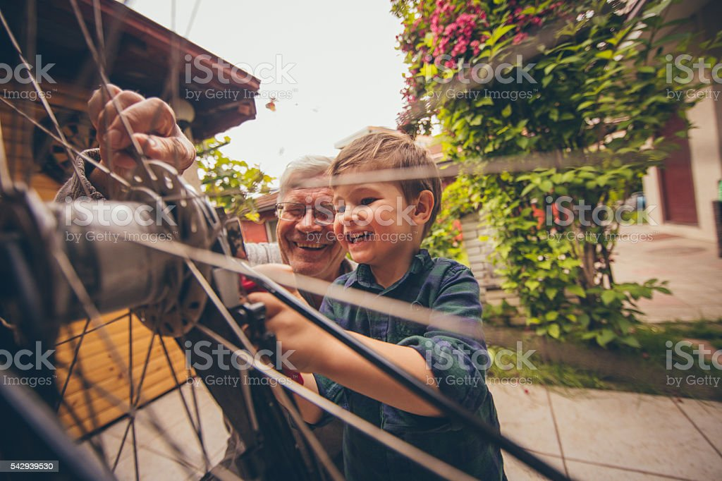 Little repairman and his grandfather stock photo