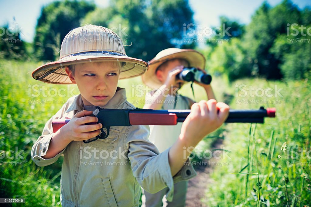 Little safari boys exploring dangerous widerness stock photo