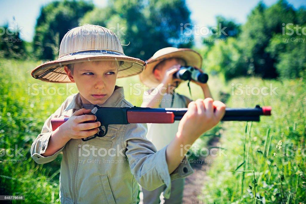 Little safari boys exploring dangerous widerness stock photo