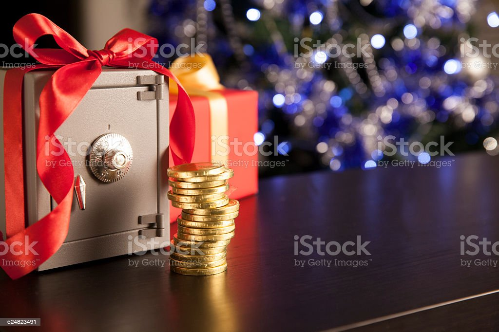 Little safe with red ribbon and golden coins stock photo