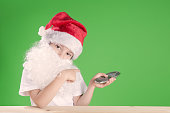 Little Santa Claus looking at the camera head bowed. Сhromakey