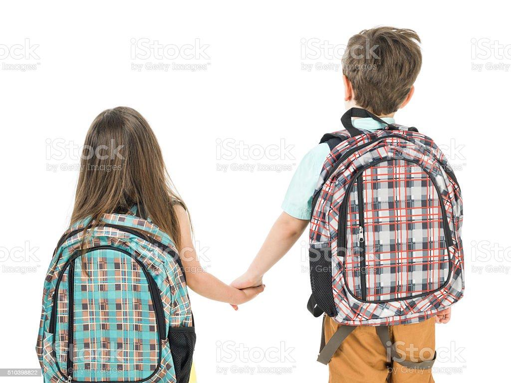 Little School Girl And Boy Walking Hand In Hand stock photo