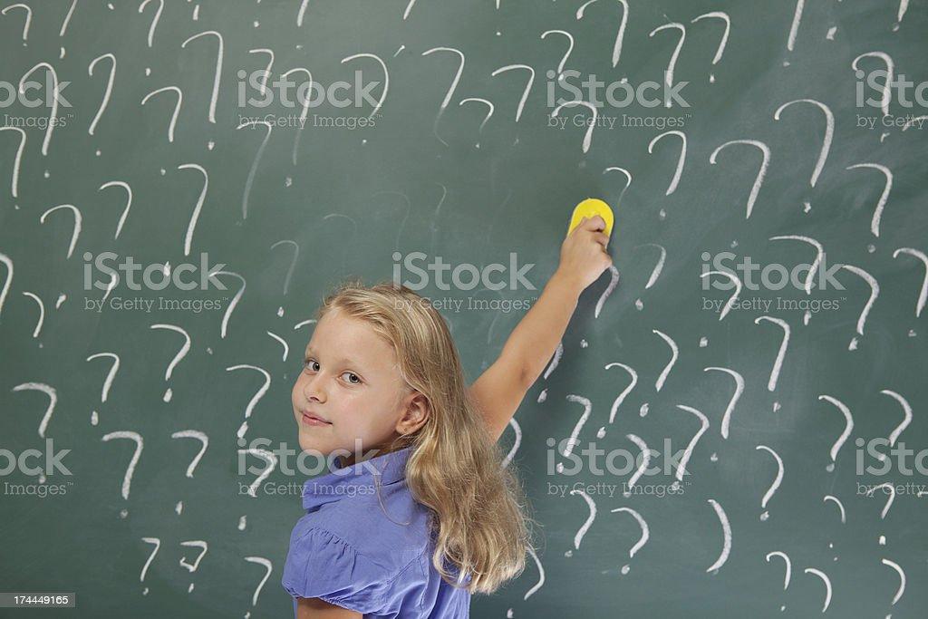 Little school girl erasing question marks on blackboard royalty-free stock photo