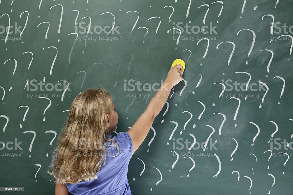 Little school girl erasing question marks on blackboard royalty-free stock photo