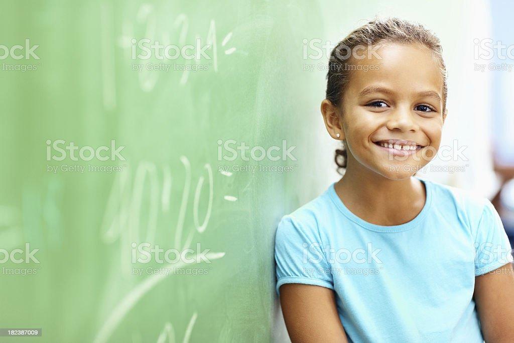 Little school girl leaning on board stock photo