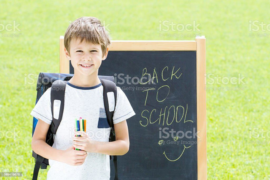 Little schoolboy with pens and backpack against the blackboard. Education stock photo