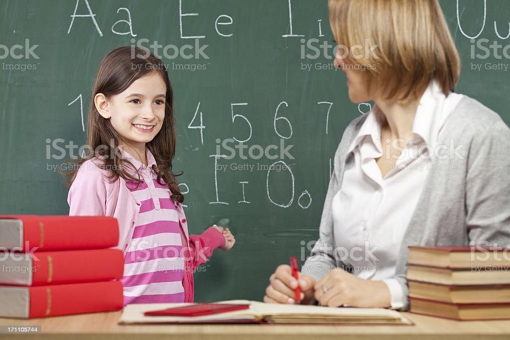 Little schoolgirl and her teacher royalty-free stock photo