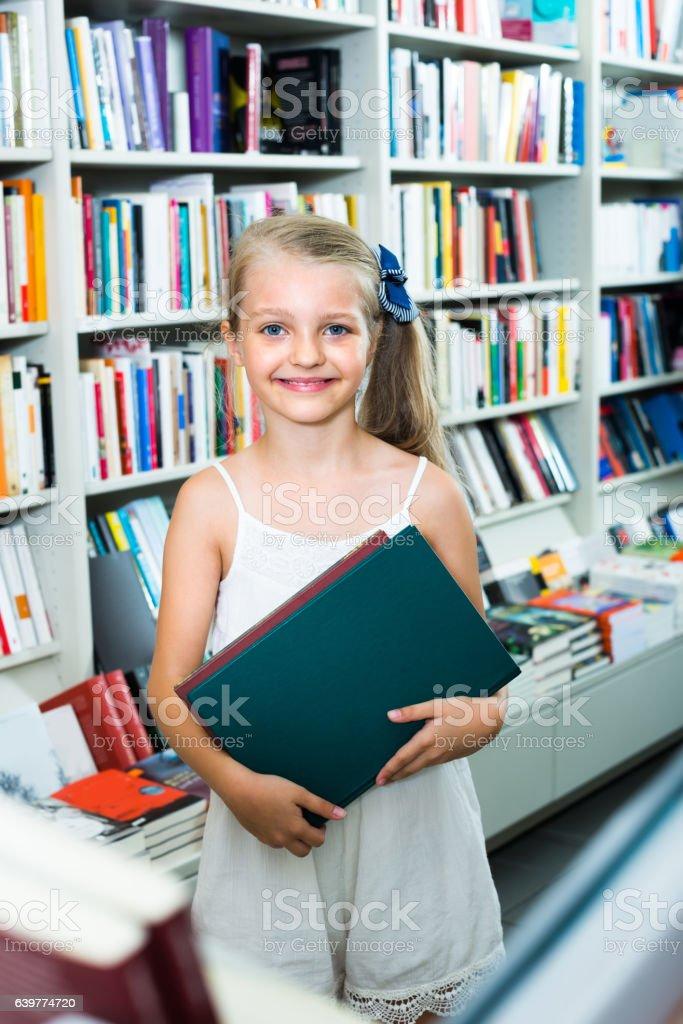 little schoolgirl in book shop stock photo