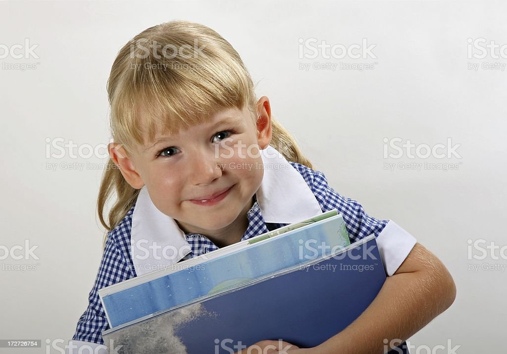 Little schoolgirl in school uniform holding books royalty-free stock photo