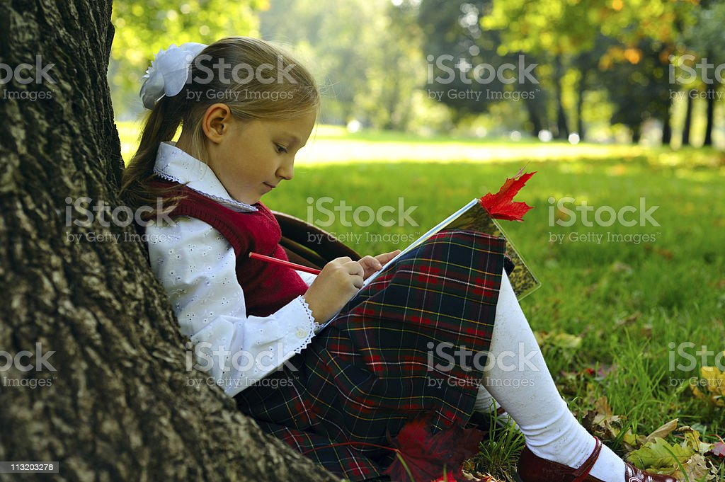 Little schoolgirl in the park royalty-free stock photo