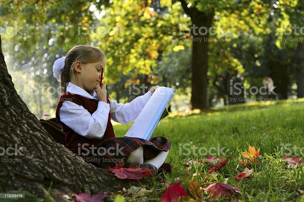 Little schoolgirl in the park royalty-free stock photo